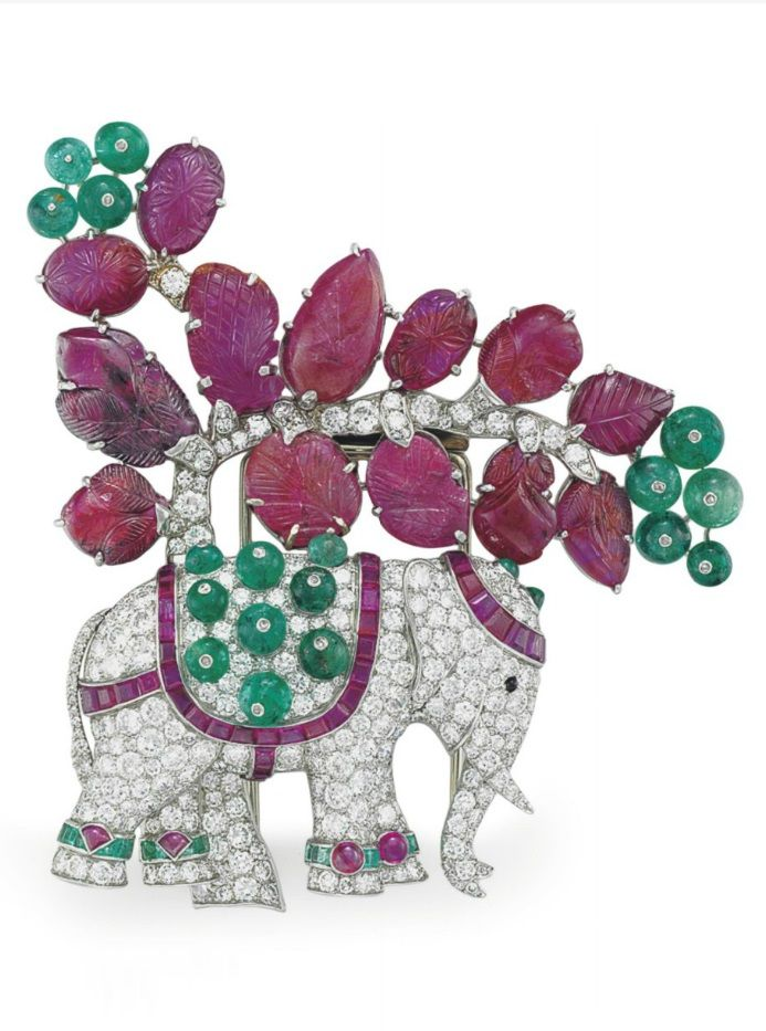 RENÉ BOIVIN - AN ART DECO RUBY, EMERALD AND DIAMOND ELEPHANT BROOCH, CIRCA 1939. Designed as an old-cut diamond elephant, with calibré-cut ruby and cabochon emerald headdress, onyx eye, calibré-cut ruby and emerald bead saddle and calibré-cut emerald and cabochon ruby anklets, to the old-cut diamond tree with carved ruby leaves and emerald bead fruit, 3 1/2 ins., with French assay marks for platinum, with maker's mark. #Boivin #ArtDeco #brooch