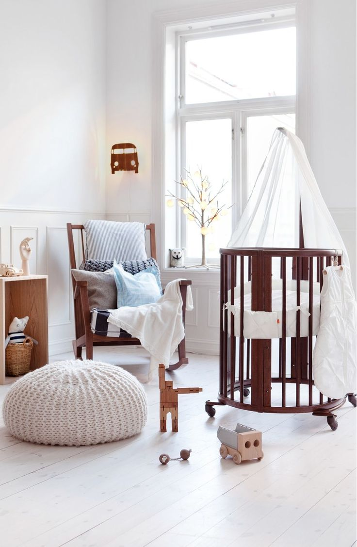 Cradling the newborn in this beautiful oval-shaped crib with a minimalist  design that matches
