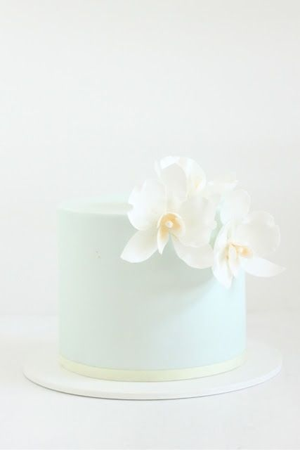 palest blue wedding cake with a pure white orchid. simplicity itself but so chic