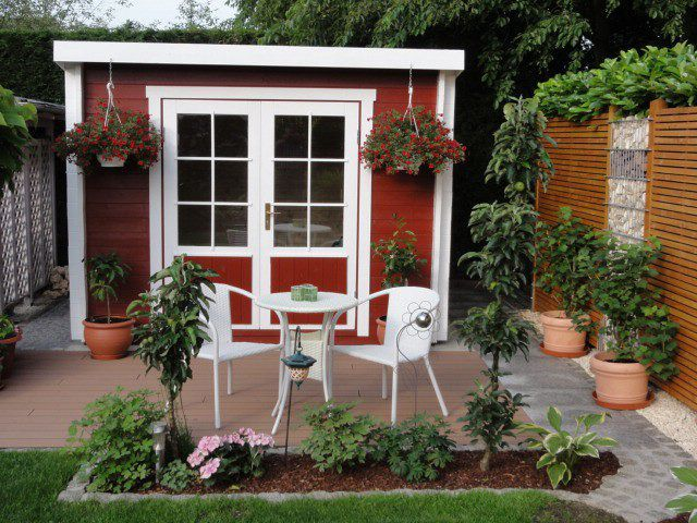Vor dem Karibu Gartenhaus Moosburg 1 laden viel Grün und bunte Blumen zum Verweilen auf der Terrasse ein.