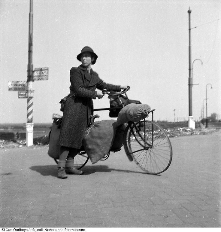 Vrouw loopt in de hongerwinter met een fiets, beladen met zakken voedsel, over een landweg nabij Amsterdam (1944-1945)