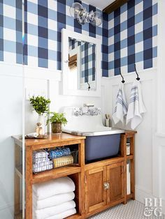 Blue and white bathroom with vintage sink painted blue on the front and blue and white gingham wallpaper.