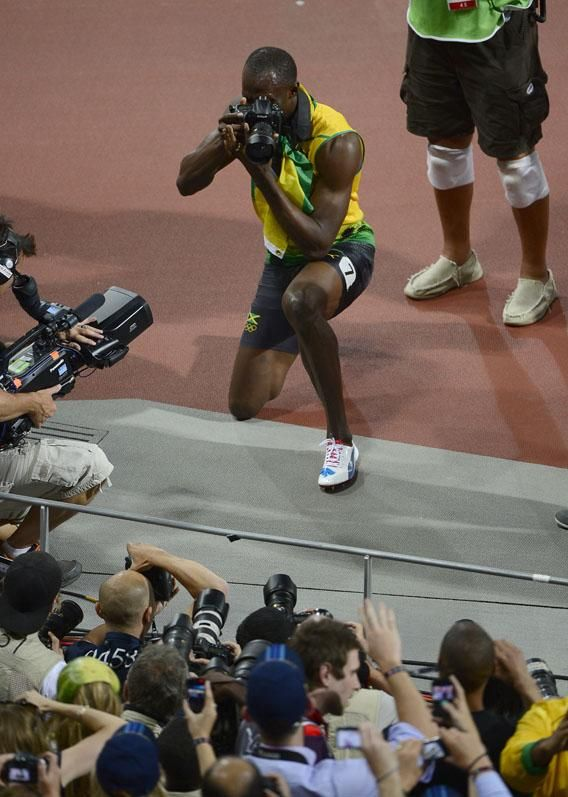 This is what a photographer who makes $ 10,000,000 per year looks like.  ::  Jamaica's Usain Bolt uses a photographer's Nikon D4 camera as he reacts after victory in the men's 200m final at the athletics event during the London 2012