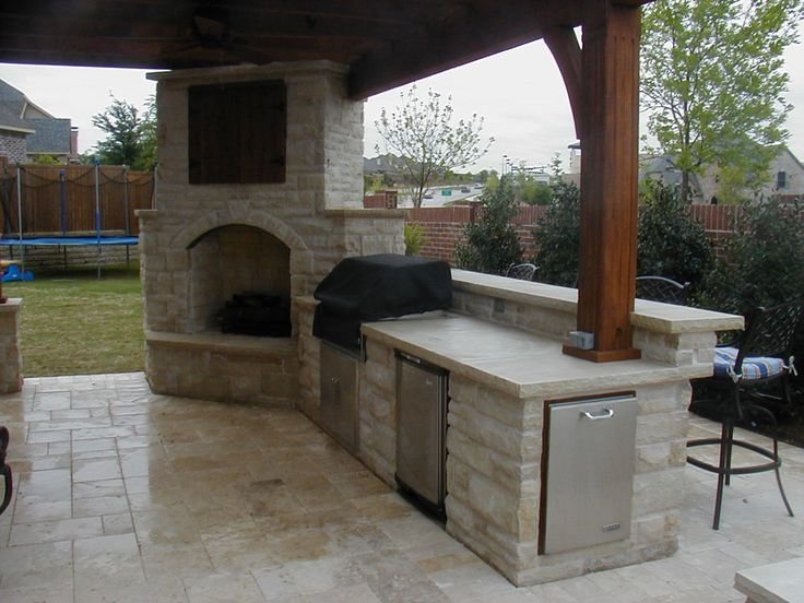 Outdoor Fireplace with covered TV, connects to outdoor kitchen. Love the design and stonework!