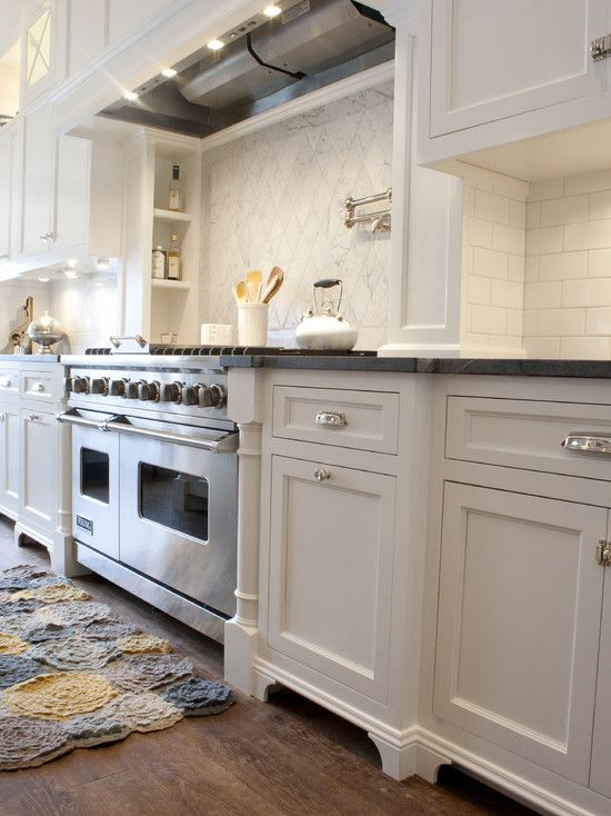 decorpad - Alice Lane Home  White cabinetry with soapstone counters, white subway tiled backsplash with carrara marble diamond tile over stove top. Polished nickel hardware, pot filler and wood floors.