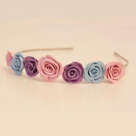 A DIY tutorial on how to make pretty clay roses for a fashionable headband.