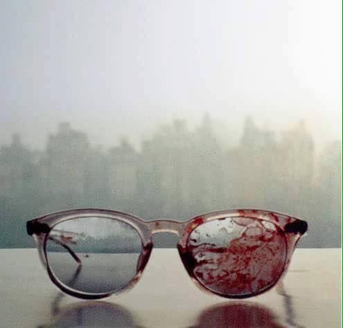 Gli occhiali insanguinati di John Lennon indossati dal cantante il giorno del suo omicidio (l'8 dicembre 1980). La foto venne scattata dalla moglie Yoko Ono. La donna arrivò a casa, appoggiò gli occhiali sul tavolo, si fece un gin liscio e scattò la foto.