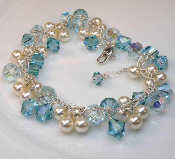 An artisan cluster bridal bracelet is handmade with gorgeous  aquamarine blue Swarovski crystals and off white Swarovski pearls.