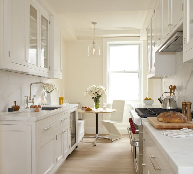 White galley kitchen and banquette seating by Alyssa Kapito Interiors https://instagram.com/alyssakapitointeriors/