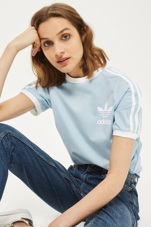 Embrace the sporty look all year round with the iconic 3-stripe tee in a summery blue update. Finished with the trefoil logo to the front, we're tucking into high waist jeans for a laidback feel. By Adidas Originals.