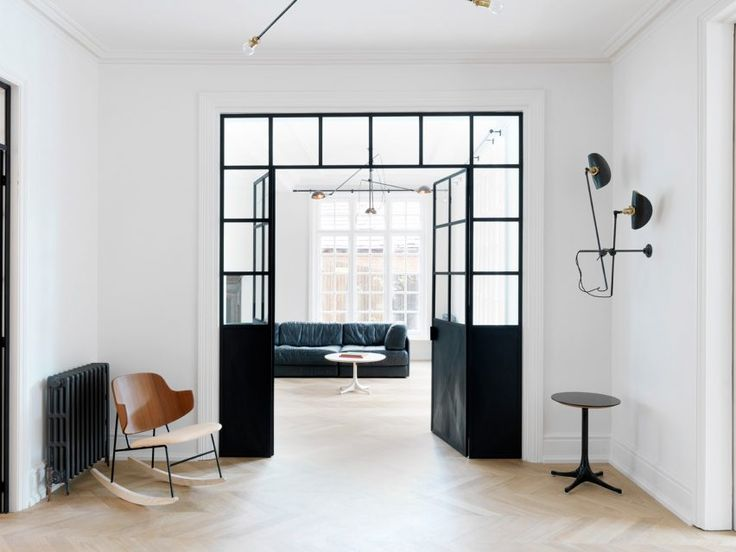 British interiors firm Studio MacLean used monochrome paintwork, oak chevron flooring, and cherry wood and marble finishes to overhaul this London house.