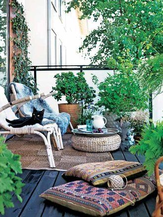 kilim rug pillows, lots of plants, jute or sisal or natural rug, white wicker or rattan chair, black decking. Good stuff.