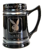 """Playboy Mug Circa 1975 with the Playboy Bunny on the side. The mug is black and features the inscription """"Playboy of the Year"""" and the date 1975. The mug is 5 3/4"""" Tall and measures 4"""" in diameter at the bottom. The mug was manufactured in the USA and is marked with L-18 on the base."""