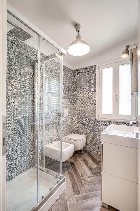 Los sanitarios de este otro cuarto de baño presentan líneas rectas y una estética muy moderna. Tanto el lavabo, como el inodoro y el bidé. Todos ellos suspendidos sobre el suelo para no recargar el espacio. De esta forma, al percibir el suelo en su totalidad, apreciamos la estancia mucho más amplia. A esto también ayuda la ventana que deja pasar gran cantidad de luz natural, y la ducha con cerramiento acristalado, que permite ver la pared de azulejos como si de una composición artística se…