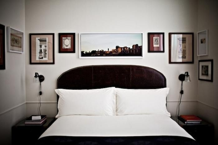 He'd would kill me for this many holes in the wall but I Love the way the pics are hung.  Art above curved headboard