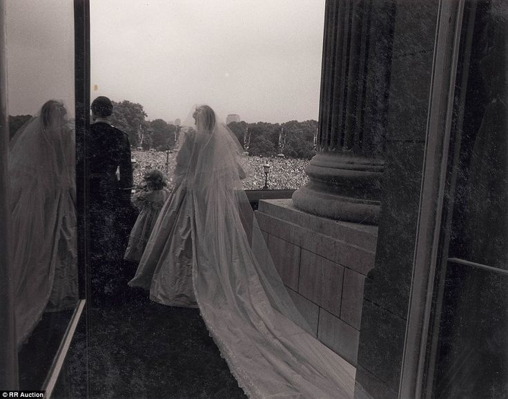 This behind-the-scenes shot shows Prince Charles and Princess Diana stepping out on to the balcony to greet thousands of well-wishers