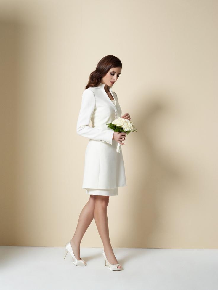 Wir von DOLZER empfehlen für die standesamtliche Trauung das Etuikleid in strahlendem Weiß und edlen Materialien. Je nach Geschmack können Sie unsere Etuikleider mit hohem oder tiefem Ausschnitt und mit oder ohne Ärmelchen bestellen. Der elegante Gehrock Julie mit extravagantem Stehkragen und stoffbezogenen Knöpfen komplettiert das Ensemble und wärmt die Braut an kühleren Tagen.