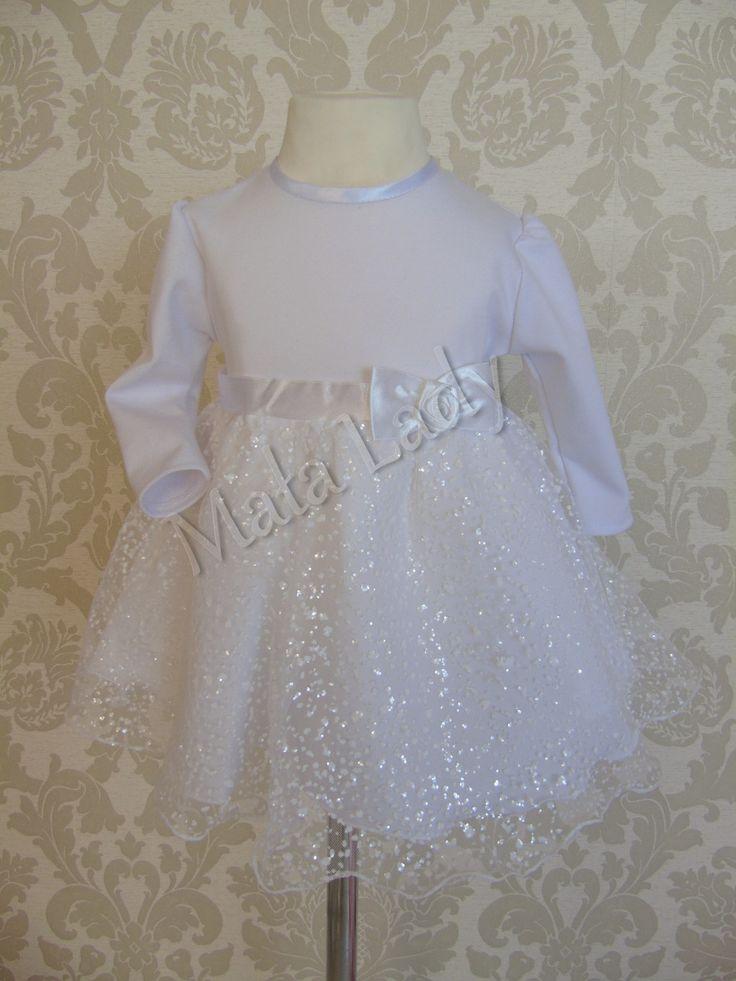 Sukienka Natalia wykonana z białej dzianiny punto oraz mieniącego się tiulu z brokatem. Odszyta płótnem bawełnianym oraz podszewką. Sukienka posiada długi rękaw oraz kryty zamek z tyłu kreacji. Możliwość dopasowania sukienki do ciała dzięki wiązanym z tyłu atłasowym paskiem.