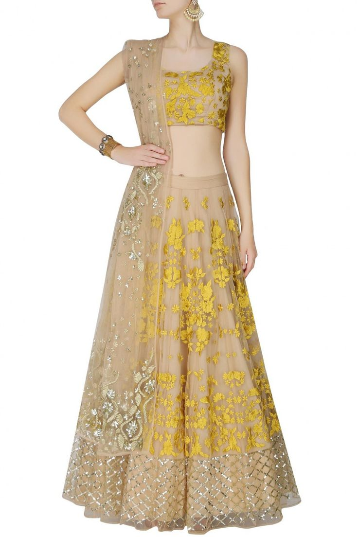 This set features a light peach lehenga in net base appliqued with yellow thread floral embroidery all over the front and back and criss cross sequins border ar