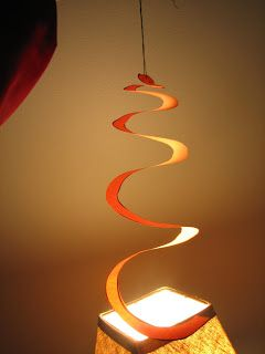 Heat transfer by convection causes the spiral over the light bulb to spin.