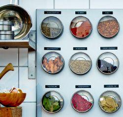 Cozinha com arrumação de especiarias feita com recipientes e quadros magnéticos. Quadro magnético prateado, fixado numa parede com azulejos brancos, com recipientes em aço inoxidável com tampas transparentes.
