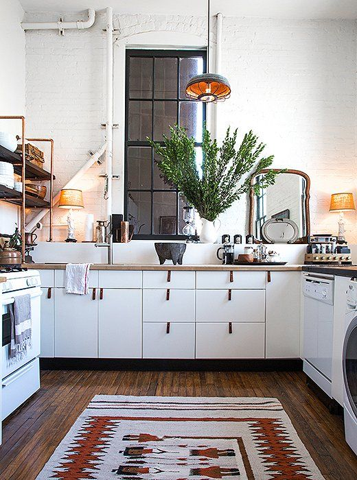 Classic white kitchen cabinets get a rustic update with leather drawer pulls and a vintage Navajo floor runner.