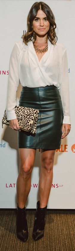 Who made  Nikki Reed's black leather skirt, leopard clutch handbag, gold jewelry, and white long sleeve top?