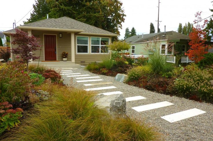 Erin Lau Design: ornamental grasses and colorful plants give year round interest. The gravel path is paved with concrete step stones. Plants flanking the path are grown in existing mounds for added height.