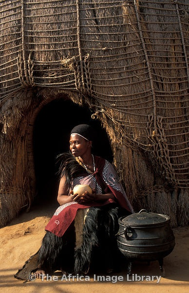 Swazi woman drinking from a calabash in front of a beehive hut, Matsamo village, Swaziland