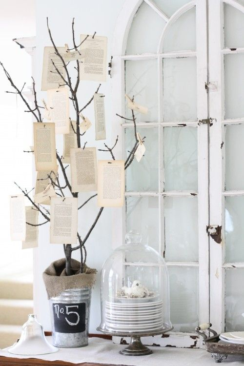 Recycle, reuse and reinvent something beautiful. In this lovely vignette, a book tree crafted from old torn pages naturally coexists with salvaged palladian windows. A repurposed cloche reinforces the shabby chic aesthetic.