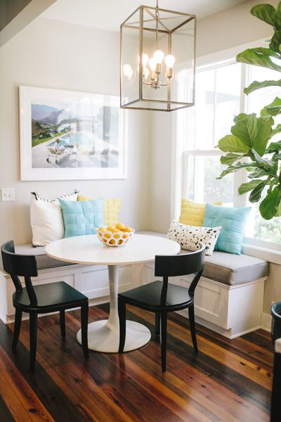 Round table and corner banquette dining area | bright pillows