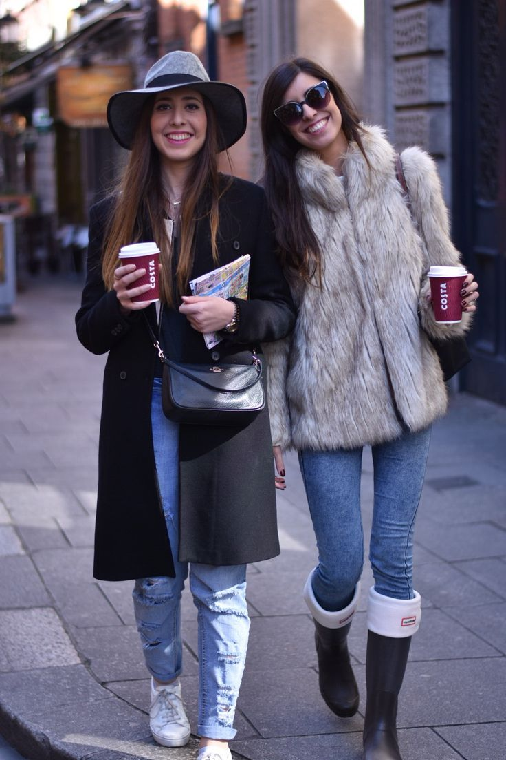 Lucía and Claudia Peris in Dublin wearing ripped boyfriend jeans, black maxi coat, grey hat, cross body bag, white sneakers, faux-fur coat, skinny jeans, hunter boots and socks, and cat-eye sunglasses (midilema.com)