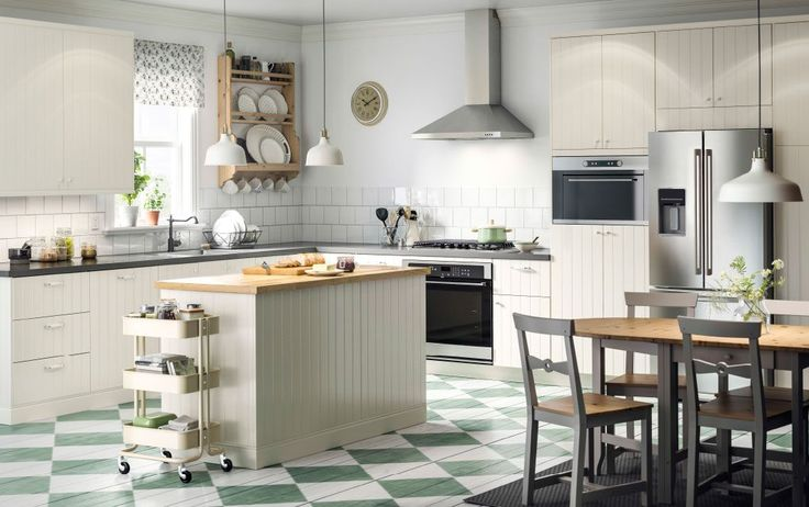 A large country kitchen with off-white drawers, doors and a kitchen island. Combined with grey chairs and a gateleg table with solid pine table top and grey legs.