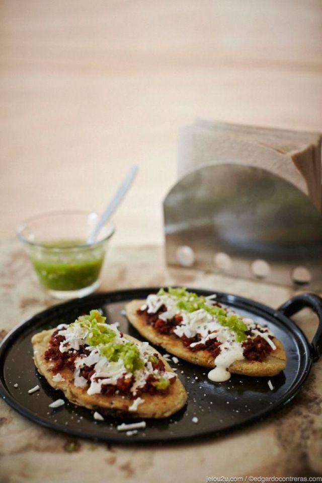 Tlacoyos de frijol con chorizo, queso, crema y salsa / Black bean tlacoyos with chorizo, cheese, cream and salsa.