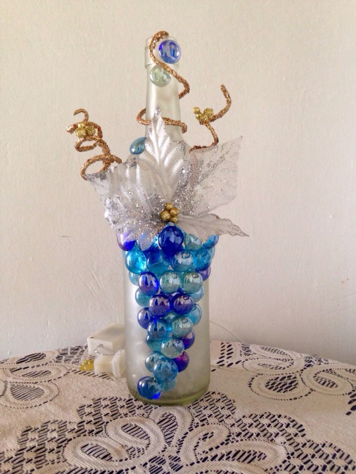 Botella de vidrio decorada con gemas, hojas artificiales y luces navideñas
