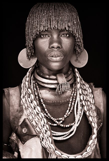 Ethiopia by John Kenny.  It is likely that this person resides in Mago National Park in Ethiopia. Areas along the lower Omo (within the park) are populated with a rich diversity of ethnic groups, including the Aari, Banna, Bongoso, Hamar, Karo, Kwegu, Male and Mursi peoples. See: http://en.wikipedia.org/wiki/Mago_National_Park