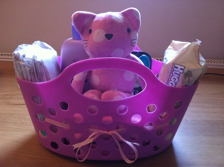 Baby girl gift basket - filled with baby wipes, disposable changing mats, bubble bath, feeding spoons, tummy butter for Mum, baby grow, dribble bib and a soft toy cat. The basket is meant for pegs but thought it would make a great container in the nursery for toys etc.