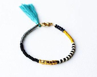 Envuelva el brazalete con borla, pulsera moldeada, Mala pulsera, joyería de Yoga  Este listado está para un abrigo pulsera en oro con perlas de jaspe negro redondo y una borla multicolor y crudo.  Detalles: -Japonés de cristal granos de la semilla, -24K oro plateado cuentas de bronce, -negro perlas de jaspe, -seda del bordado, -conclusiones y cierres, chapado en oro -cable flexible, -aprox. 14,75 L (diseñado para adaptarse a 7 muñeca)  Todos los artículos de fieltro como papel llegan en…