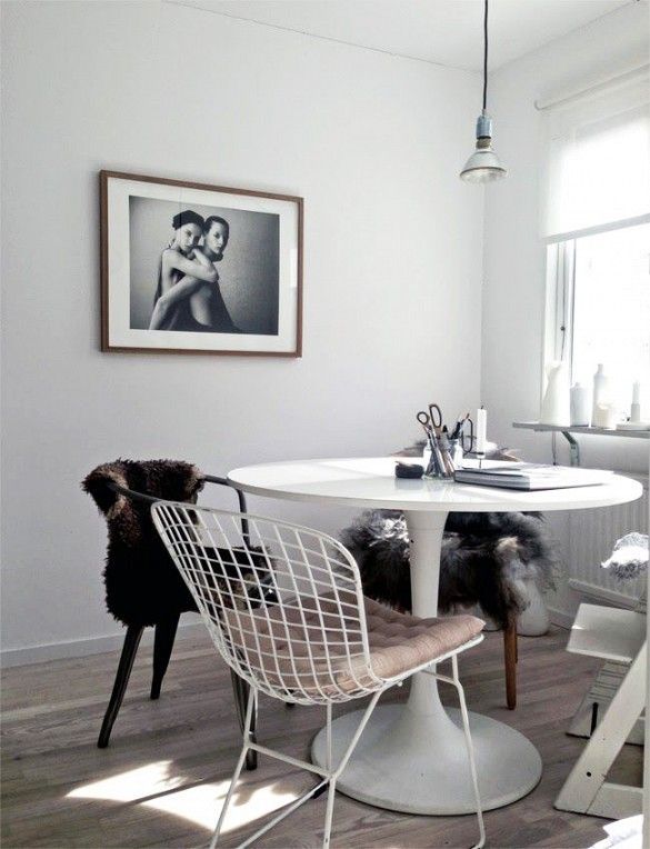 Monochrome white dining space with framed fashion print and IKEA Docksta table.