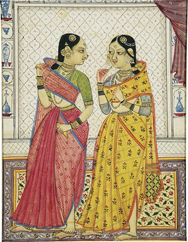 Two courtly ladies. By Bihari, India, Bikaner, in Golconda style, circa 1700. Two elaborately bedecked ladies standing on a floral carpet, the lady at right clad in a lengha with gold waistband over a printed blue choli, glancing at her companion who turns profile to meet her gaze, the companion in a rose lengha and dupatta with green choli, each holding a betel case, within an interior painted with blue-and-white ceramics,