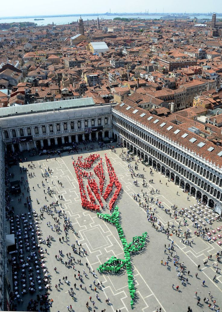 """Over one thousand residents of Venice participate in composing this living rosebud in St. Mark square in Venice, on occasion of the """"Festa del Bocolo,""""a tradition dating back to the Middle Age, Friday, April 25, 2014. On this day, which is also the day when St. Mark, patron saint of Venice, is celebrated, men traditionally give a rosebud to the women of their family and to their loved one."""