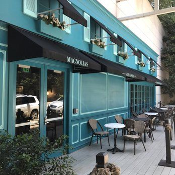 Photo of Magnolias Sous Le Pont - Dallas, TX, United States. The front of coffee house and patio looks like it was transplanted from Paris. Always in the shade as surrounding buildings block the sun.