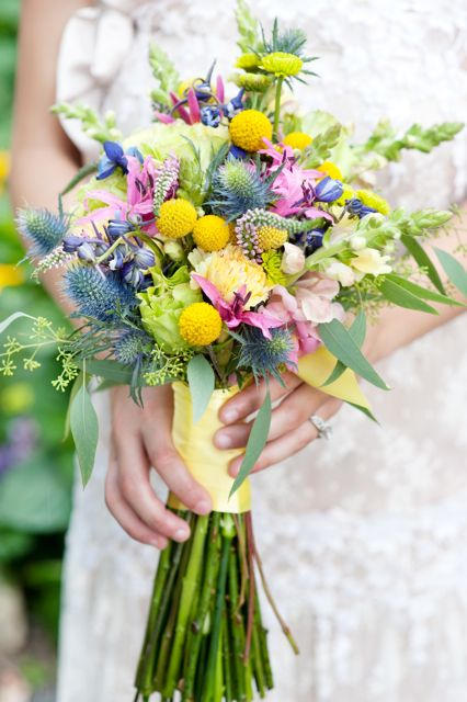 Thistle, Delphinium, Billy buttons, Snapdragons, green roses, yellow carnations, pink nerine lily, pink veronica.