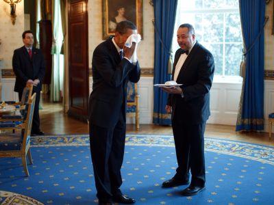 President Obama veegt zijn gezicht af met een doekje dat hij krijgt van butler Von Everett.