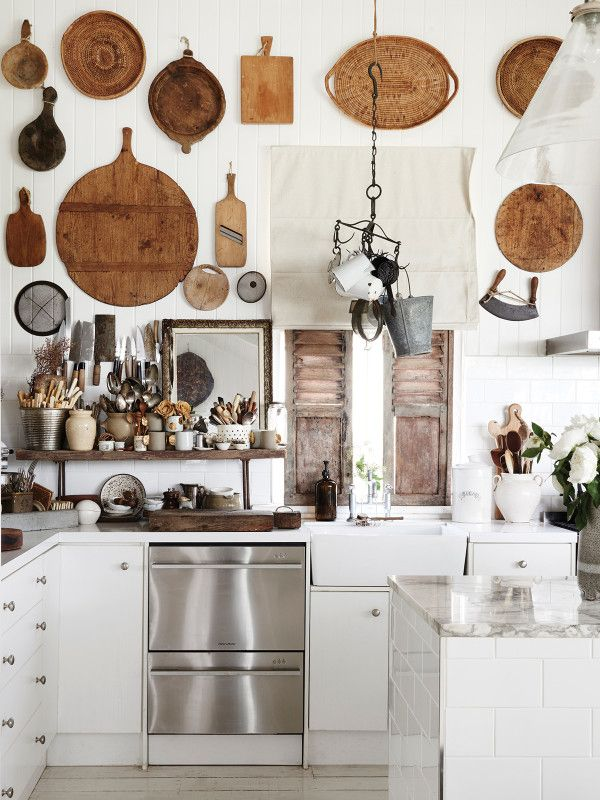 Dig this modern rustic kitchen with those vintage cutting boards and marble countertops. Great mix of luxe and rough textures.