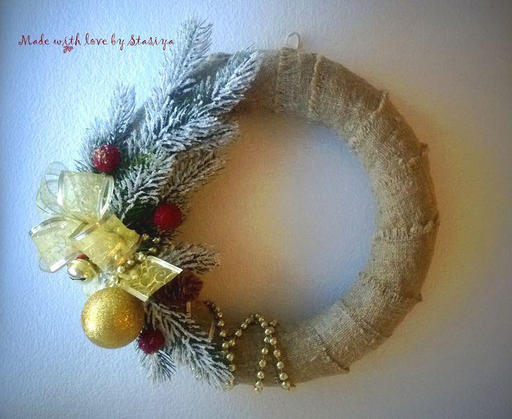 Чудесный новогодний веночек принесет радость и новогоднее настроение в ваш дом. Оформлен натуральной мешковиной, украшен искусственными ветками,имитирующими лапы ели, так же использованы настоящие сосновые шишки. Золотая гирлянда из бус придает изделию нежность и утонченность. Станет прекрасным украшением вашего дома!
