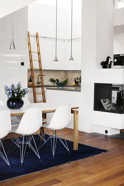 Det ljusa köket med dubbla rader köksskåp har ritats av inredaren Helene Becker och tillverkats av Claessonkök. Även stegen i ek är specialtillverkad. Arbetsbänkar i betong och stänkskydd i glas. Matbord av Strand+ Hvass, Carl Hansen & søner, lampan över, Enigma, är från Louis Poulsen. (A Swedish attic conversion that has a kitchen with a sliding ladder.)