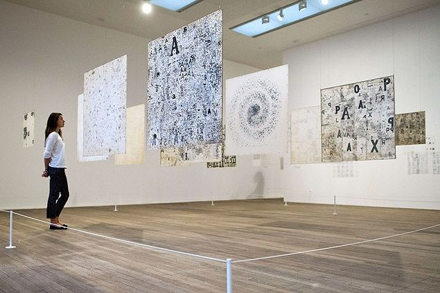 Employee observes Mira Schendel's works at Tate Modern