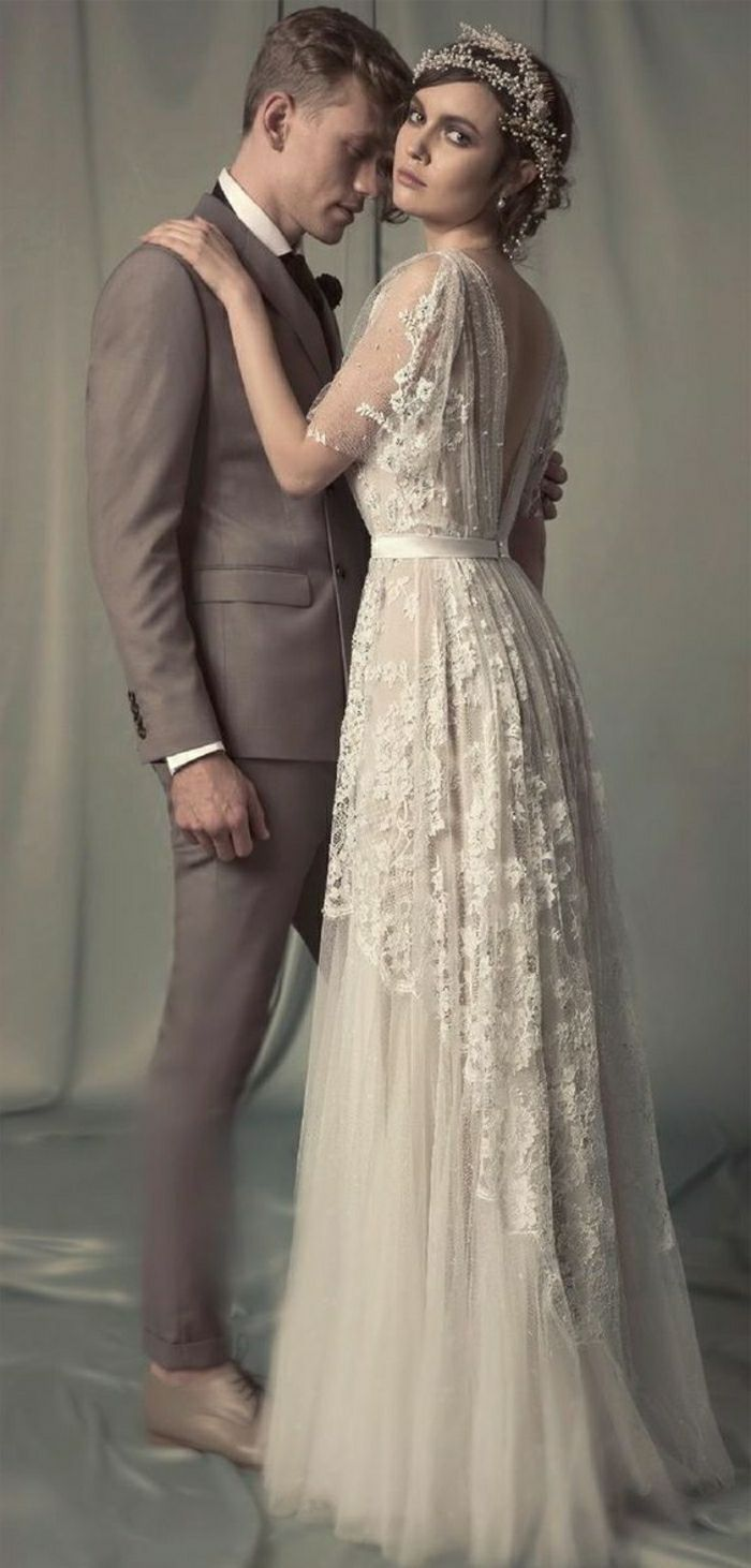 vintage inspired wedding dresses, bride in long vintage embroidered gown with lace and wearing a hair ornament hugging a man in a light brown suit