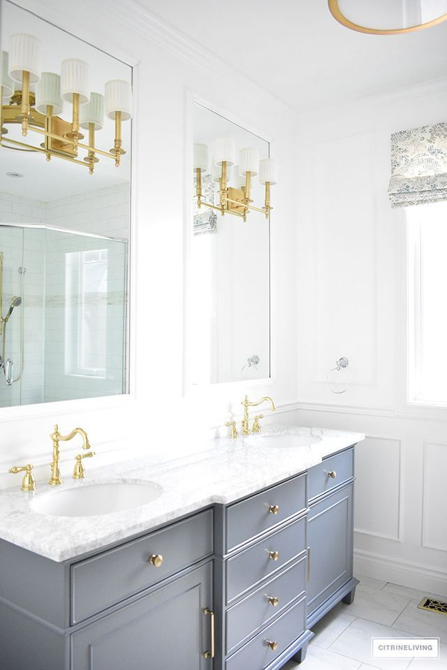Gorgeous master bathroom makeover with custom mirrors, brass wall sconces and fixtures, + elegant white panelling!